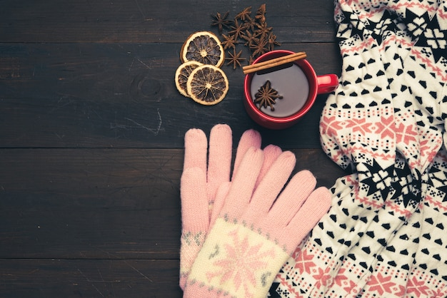Knitted mittens, scarf and red cup with a drink on a brown wooden table