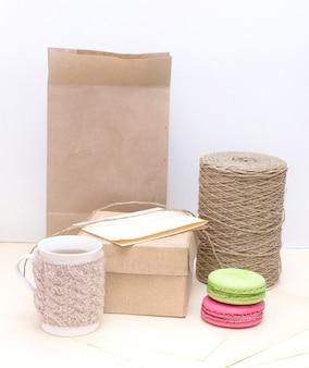 紙袋にニットマグカップ、カラフルなマカロン、段ボール箱