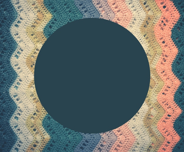Knitted multicolored cotton fabric in cold blue tones. round blue frame for text. vintage toning