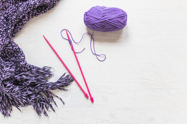 Knitted needles with purple yarn and scarf on white textured backdrop