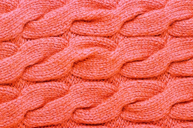 Knitted pattern trend color living coral close-up, background, texture