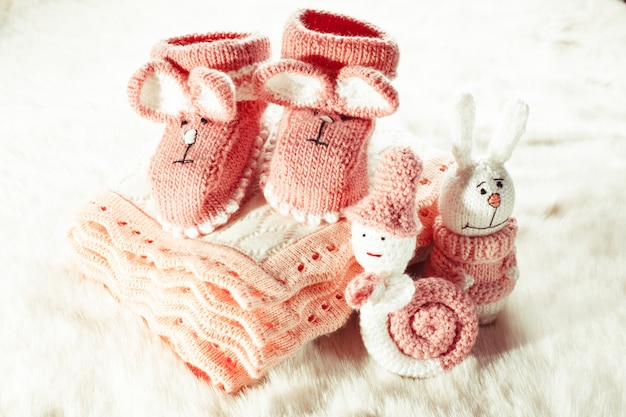 Knitted pink baby booties, toys, blanket for little girl