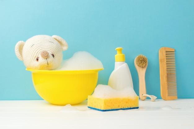 Knitted polar bear bathing in a yellow basin.