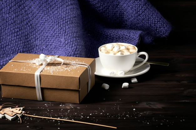 A knitted purple blanket, a cup of hot cocoa with marshmallows, on a dark wooden background