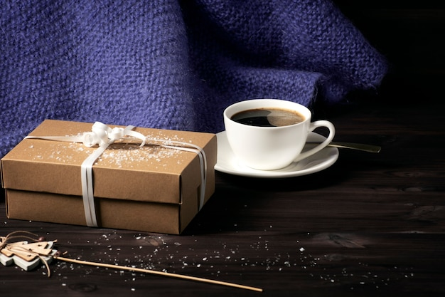 A knitted purple blanket, a cup of hot coffee and a gift box on a dark wooden background with snow.