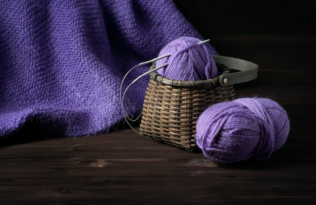 Knitted purple blanket and a wicker basket with purple yarn on a dark wooden background.