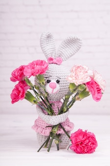 Knitted rabbit. festive decor. bouquet of carnations. valentine's day. handmade, knitted toy, amigurumi
