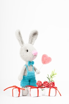 Knitted rabbit with a heart. st. valentine's day decor. knitted toy, amigurumi,  greeting card.