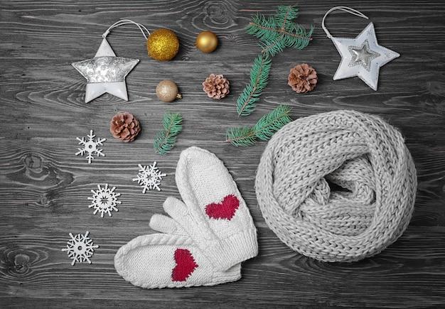 木製の表面にニットのスカーフ、ミトン、クリスマスの装飾