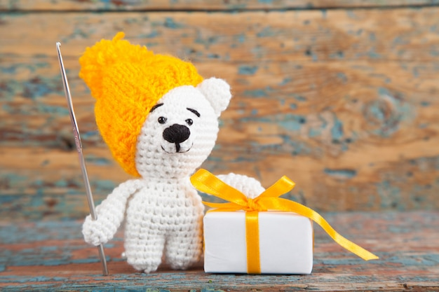 Knitted small bear on an old wooden background. handmade, knitted toy. amigurumi