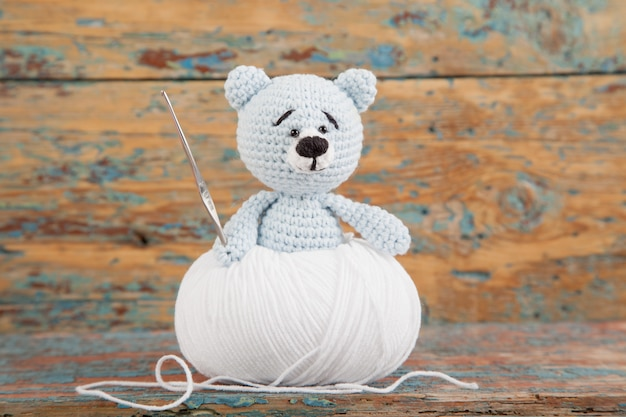 Knitted small bear on an old wooden . handmade, knitted toy. amigurumi