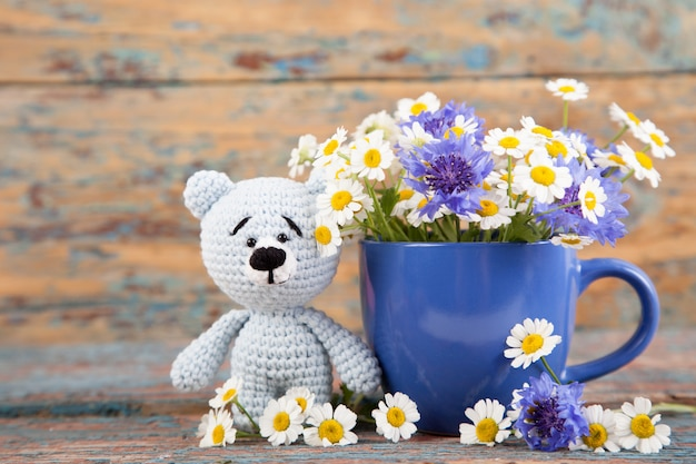 Knitted small bear with chamomile on an old wooden background. handmade, knitted toy. amigurumi