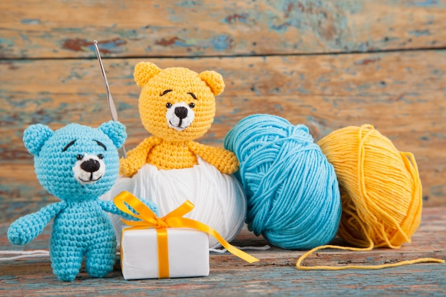 Knitted small bears on an old wooden background. handmade, knitted toy. amigurumi