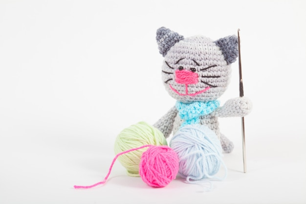 Knitted small cat on an white background. handmade, knitted toy. amigurumi