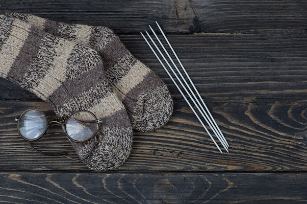 Knitted socks, knitting needles and old glasses