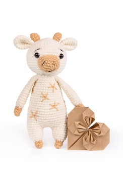 Knitted soft toy bull on white and heart