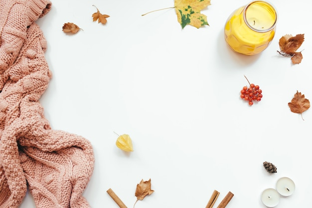 Knitted sweater, autumn leaves, cinnamon sticks, candles on white background. autumn composition. flat lay, top view, copy space