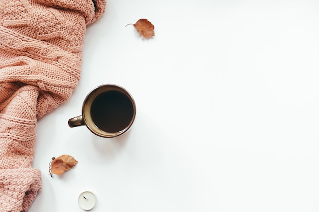 Knitted sweater, cup of coffee, autumn leaves, candles on white background. autumn composition. flat lay, top view, copy space