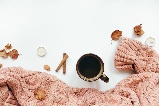 Вязаный свитер чашка кофе осенние листья палочки корицы свечи на белом фоне осень
