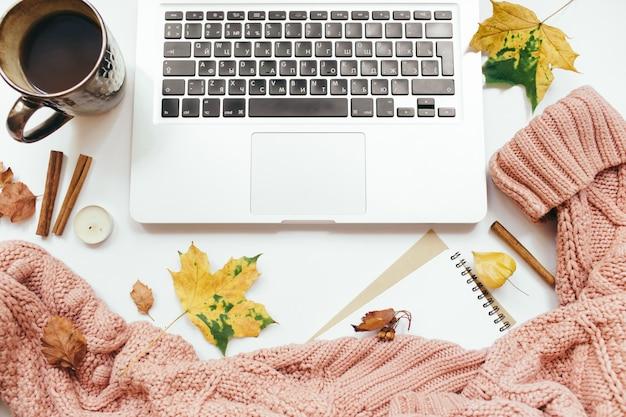 ニットセーター、一杯のコーヒー、ラップトップ、ノートブック、紅葉、シナモンスティック、白い背景の上のキャンドル。秋の構成。ホームオフィスデスクワークスペース。フラットレイ、上面図、コピースペース
