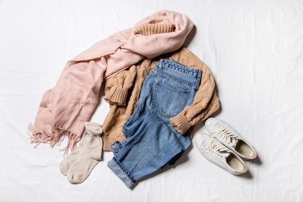 白い背景の上のニットセータージーンズと靴