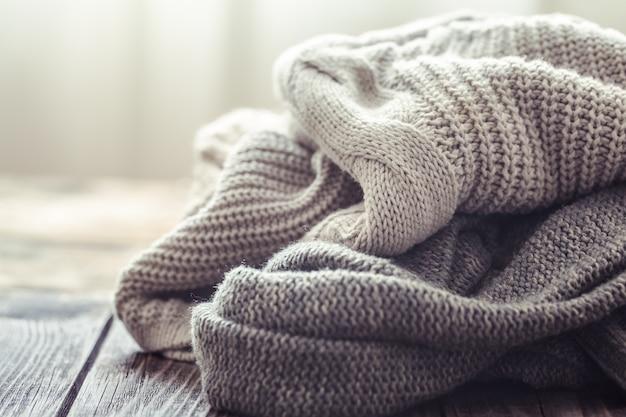 Вязаный свитер на деревянном столе
