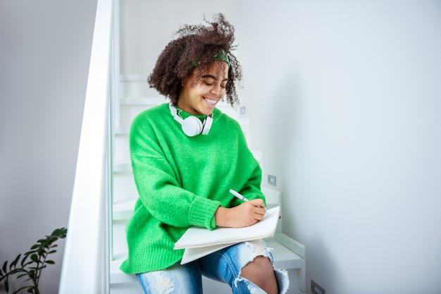 니트 스웨터. 밝은 녹색 스웨터를 입고 비행기 목록을 적어 웃는 펑키 소녀