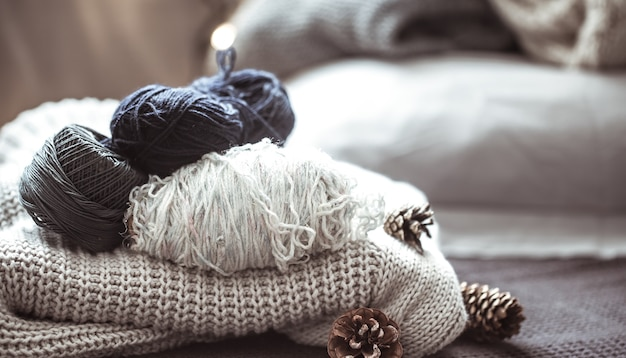 Knitted sweater with balls of yarn ,a concept of warmth and comfort, hobby , background,closeup