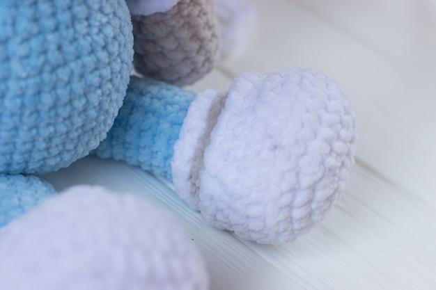 Вязаный плюшевый мишка в синей пижаме на белом фоне