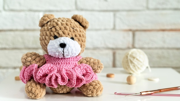 Knitted teddy bear with knitting equipment on the table
