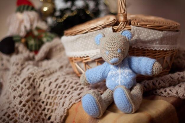セーターのニットのおもちゃのクマまたはマウスは、籐のバスケットとニットの格子縞の近くに座っています