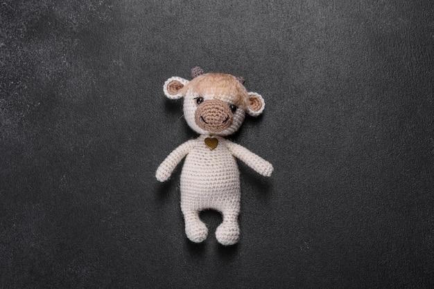 Вязаная игрушка бык из светлых ниток на темной поверхности. рукоделие, поделки своими руками
