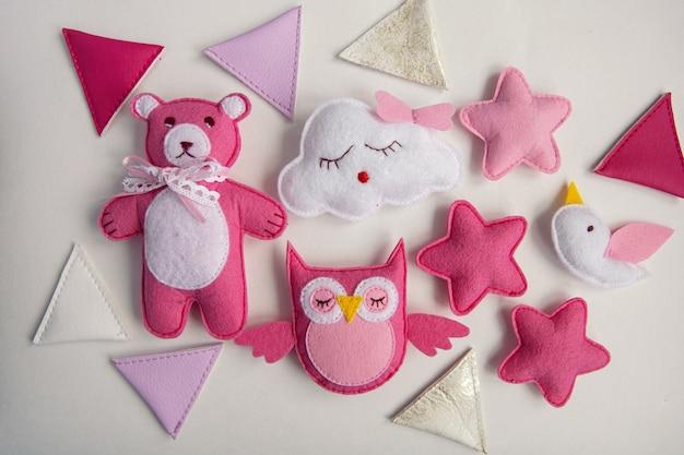 ニットのおもちゃの雲、星、クマ、ラム、フクロウ、鳥のピンクとブルーの色