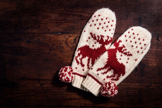 Knitted warm gloves on wood