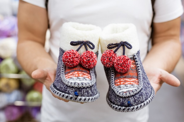 Knitted warm home slippers in the hands of a man close up