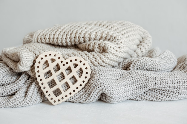 Вязаные теплые кофточки пастельных тонов и декоративное деревянное сердечко.