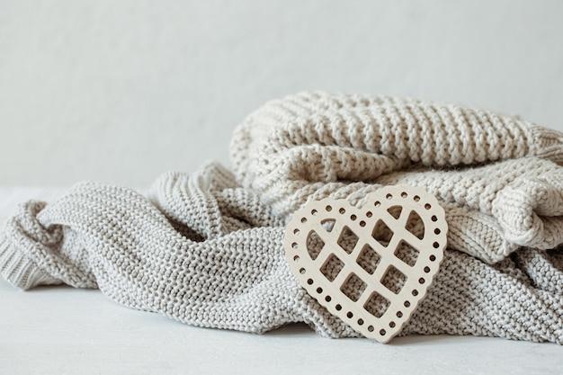 Maglioni caldi lavorati a maglia in colori pastello e un cuore decorativo in legno.