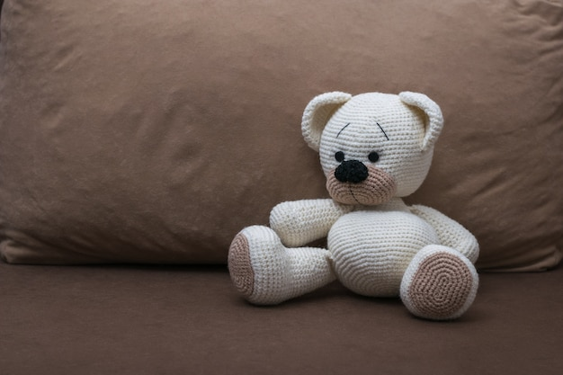 A knitted white bear cub on a soft brown sofa. beautiful knitted toy.