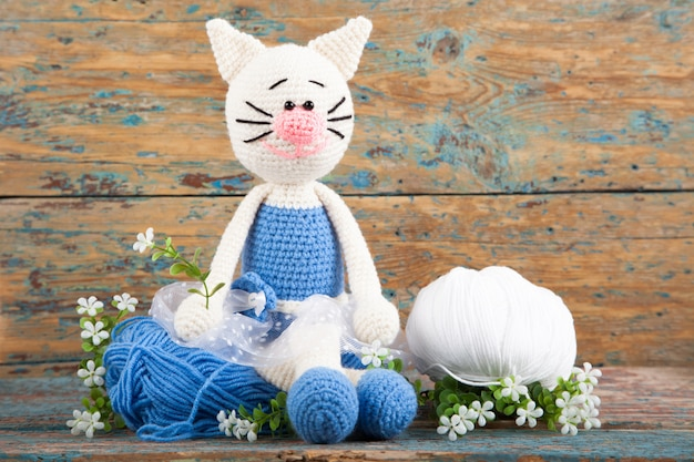 Knitted white cat in a blue dress on an old wooden background. handmade, crafts. amigurumi