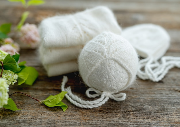 花と木製のテーブルの上に新生児のためのニットの白い服の構成。帽子をセットした幼児の羊毛の服のデザイン