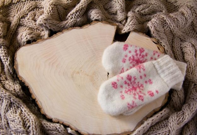 Белые вязаные варежки с розовой снежинкой лежат на деревянной.