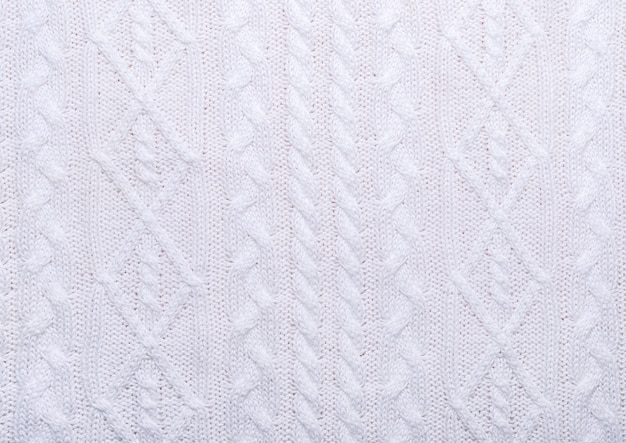 Knitted white texture with pattern of various braids.