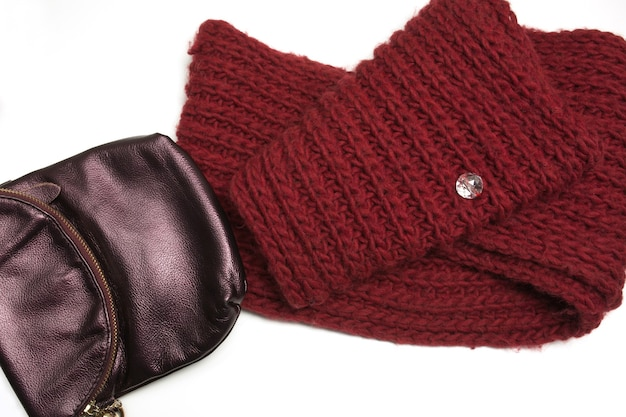 Knitted winter scarf and leather purse isolated on white background