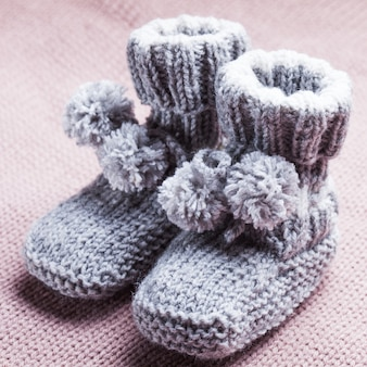 Knitted wool baby booties with pompons close up