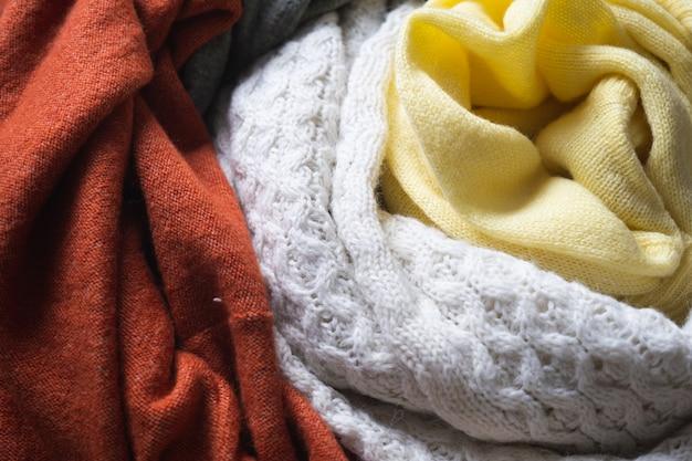 니트 울 스웨터. 니트 옷 더미와 함께 아늑한 가을 또는 겨울 배경.