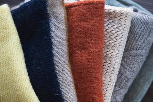 Вязаная шерстяная одежда на крупном деревянном столе. осенний или зимний фон.