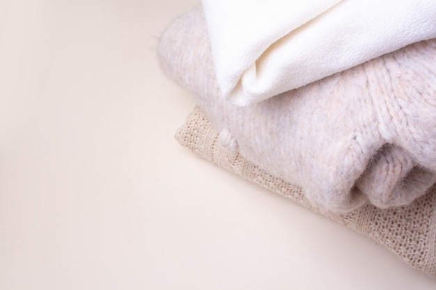 Knitted woolen sweaters on a white background. warm clothes