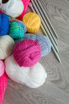 編み物。糸と灰色の木製のテーブルに針のグループ、。手作り。閉じる。上面図。コピースペース。フラット横たわっていた。