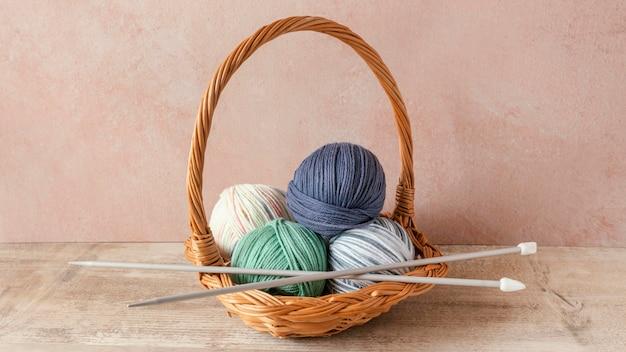 바구니에 뜨개질 바늘과 양모