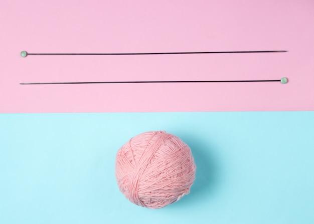 Спицы, мотки шерсти на розово-голубом пастельном фоне. вид сверху.